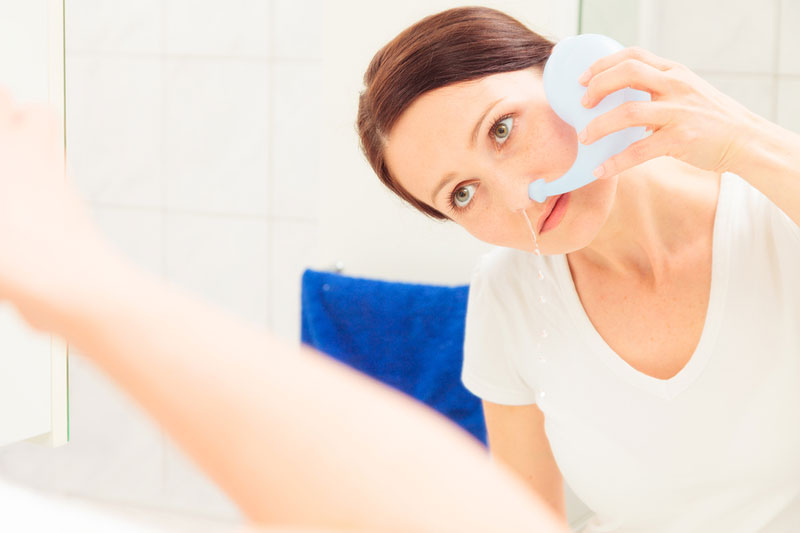 woman using a neti pot to clear her sinuses